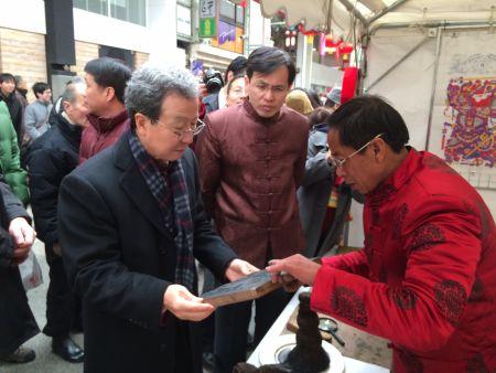 程永华大使问候山东木板年画家王圣亮。14日活动开幕仅6个小时,王圣亮就为民众制作了170多张版画。